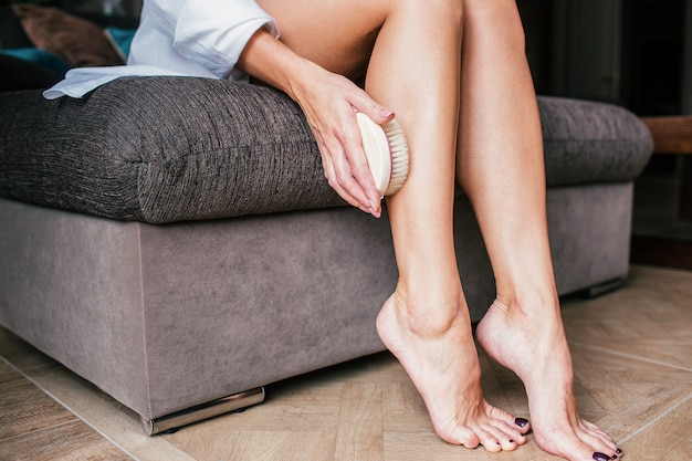Massage with a dry brush. a girl in a white shirt massages her legs in close-up on a sofa, spa, relaxation, anti-cellulite, peeling, cosmetic procedures. home skincare.