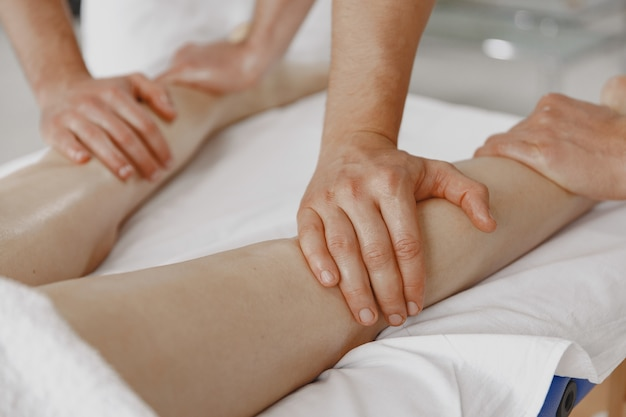 Il massaggio a quattro mani. concetto di assistenza sanitaria e bellezza femminile. due massaggiatrici fanno un doppio massaggio di una ragazza. la donna in un salone spa.