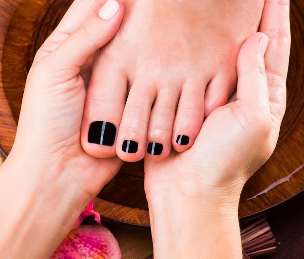Massaggio del piede della donna nel salone della stazione termale - concetto di trattamento di bellezza