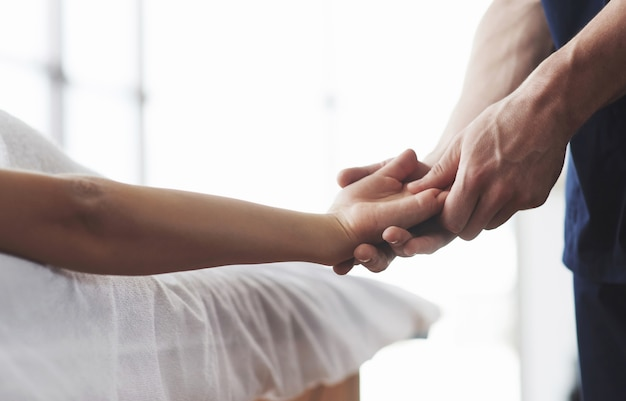 Massage of a young woman's hands, a masseur man.