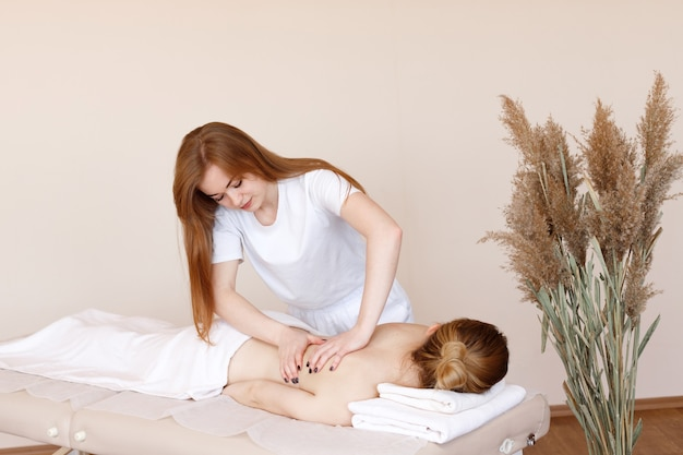 Massager does back massage to client in spa salon