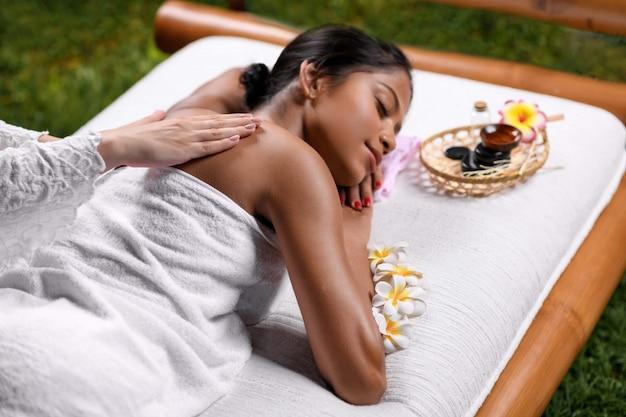 Massaging the back by a masseur of a beautiful interracial girl lying on a massage table in a white towel