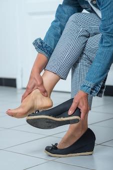 Massaging tired hurt leg due to wearing shoes