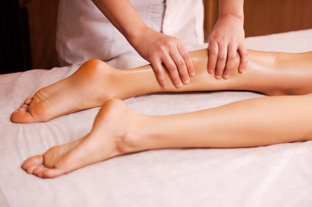 疲れた足をマッサージします。美しい女性の脚をマッサージするマッサージセラピストのクローズアップ
