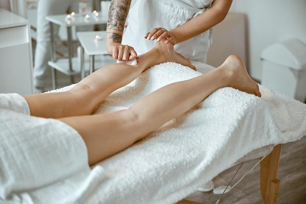 Massagist woman is doing professional leg massage in modern salon