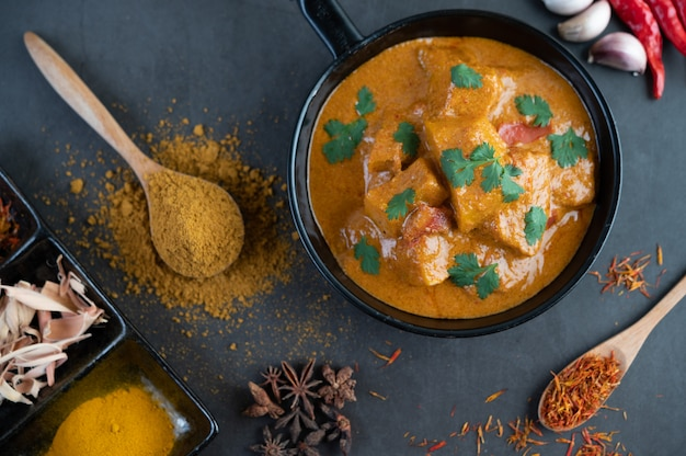 Massaman curry in a frying pan with spices on the cement floor