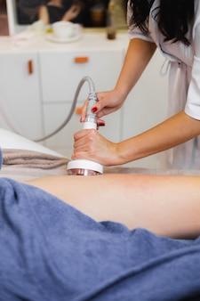 Массажист делает антицеллюлитный массаж клиенту в спа-салоне красоты с маслом