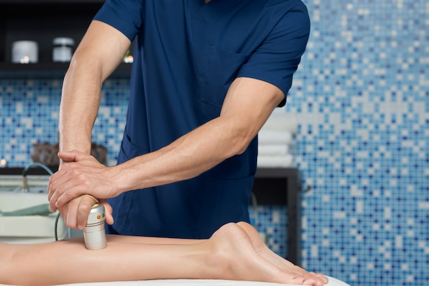 Masseur doing appartus relaxing massage of legs in spa