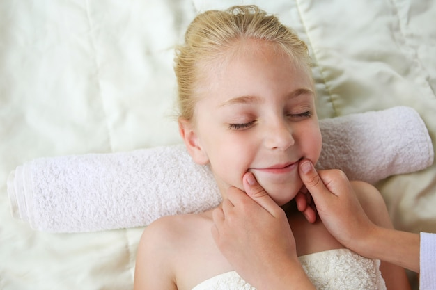 Masseur doing face massage to child.
