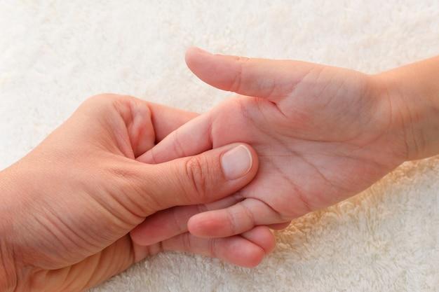 Массажист делает массаж пальцами маленького ребенка.