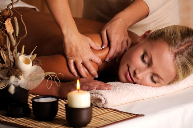 Массажист делает массаж женского плеча в салоне красоты