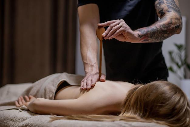 안마사는 스파 살롱에서 남자 몸에 마사지를하고. 미용 치료 개념.