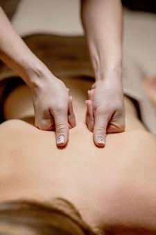 스파 살롱에서 남자 몸에 마사지를 하는 안마사. 미용 치료 개념입니다.