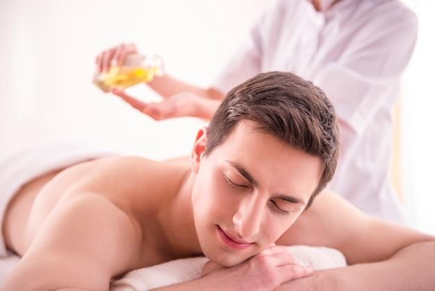 Массажист делает массаж тела человека с маслом спа.