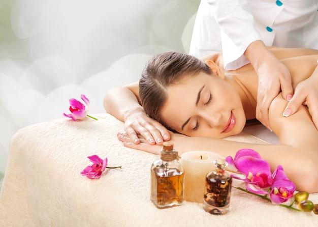 Массажист делает массаж женского тела в спа-салоне. концепция лечения красоты.