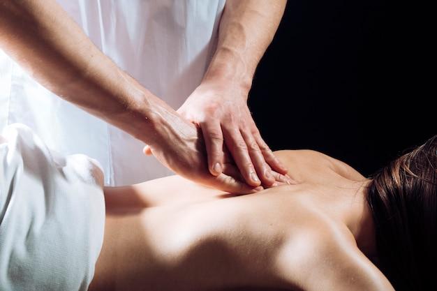 Массажист делает массаж женского тела в спа-салоне. женщина в спа-салоне, массаж.