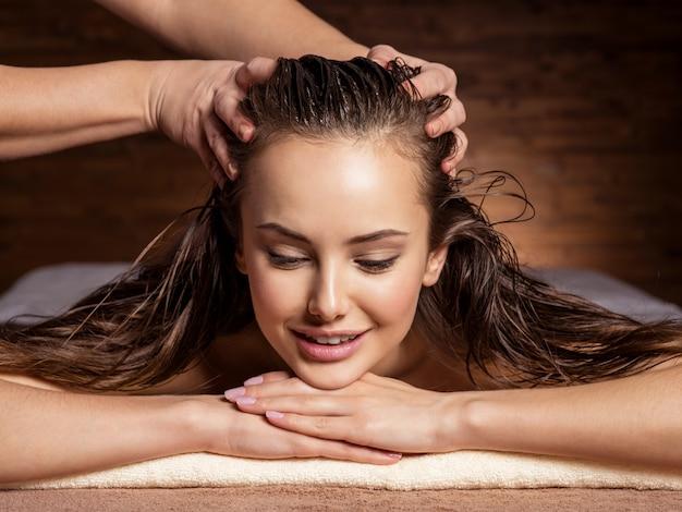 スパサロンで女性のために頭と髪のマッサージをしているマッサージ師
