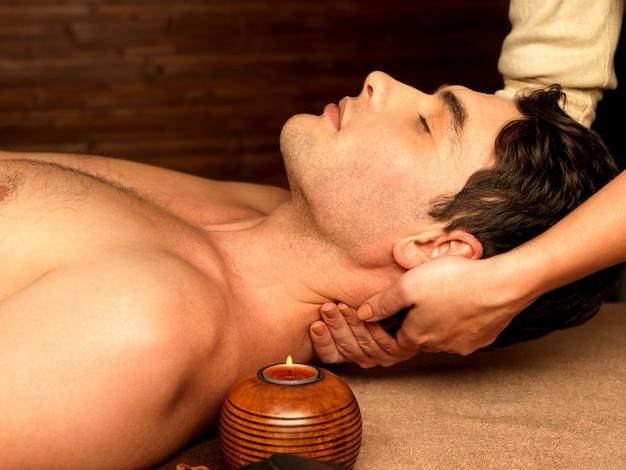 Massaggiatore che fa massaggio al collo sull'uomo nel salone della stazione termale.