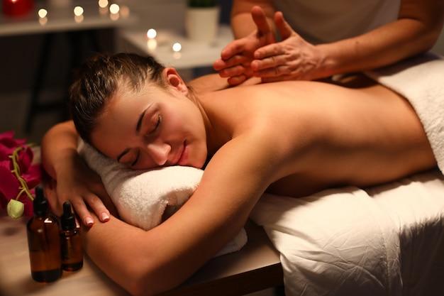 Массажист делает клиенту оздоровительный массаж спины в спа-центре.