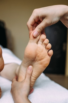 The masseur gives a massage to the female feet at the spa