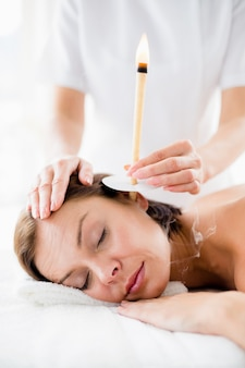 Masseur giving ear candle treament to woman