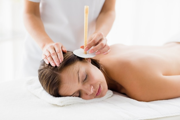 Masseur giving ear candle treatmet to woman