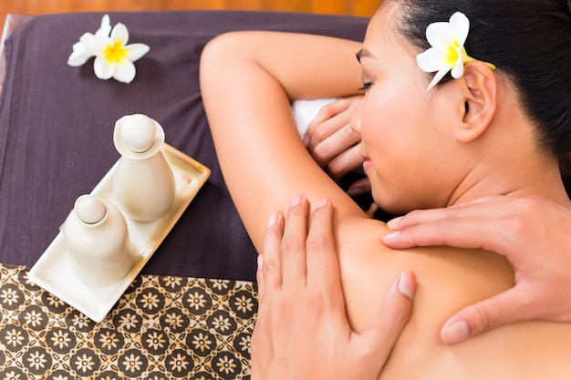 Masseur giving indonesian asian woman a aroma therapy massage with essential oil in a beauty wellness spa