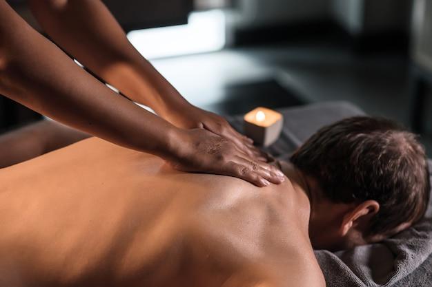 Masseur giving man neck massage in spa
