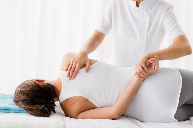 Массажист дает массаж женщине