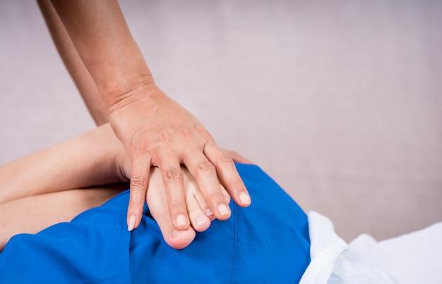 Masseur hand is massaging a woman leg