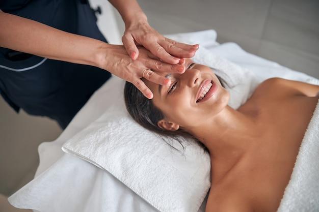 Masseur hands massaging female face in spa salon