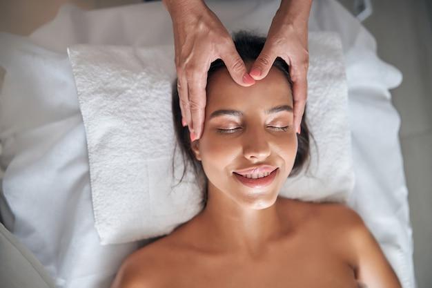 Masseur hands massaging lady face in spa salon