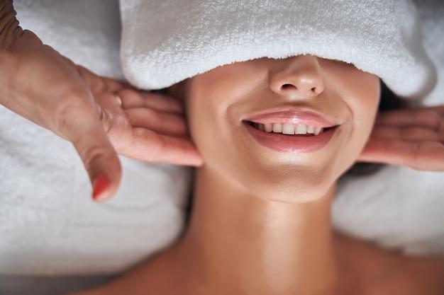 Masseur hands massaging lady neck in spa salon