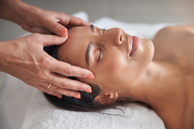 Masseur hands massaging woman forehead in spa salon