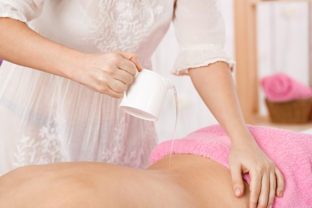 Masseur hands. pouring massage oil on woman back. relaxation concepts