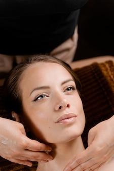 안마사는 완벽한 피부를 가진 모델을 위해 스파에서 얼굴 마사지를하고 있습니다. 미용 절차.