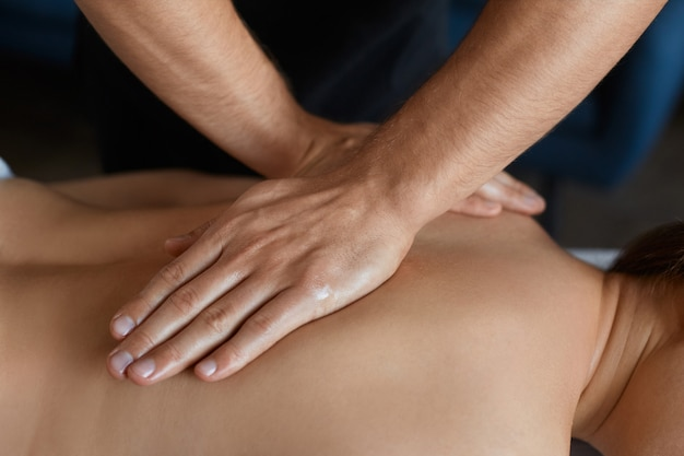 Masseur makes massage