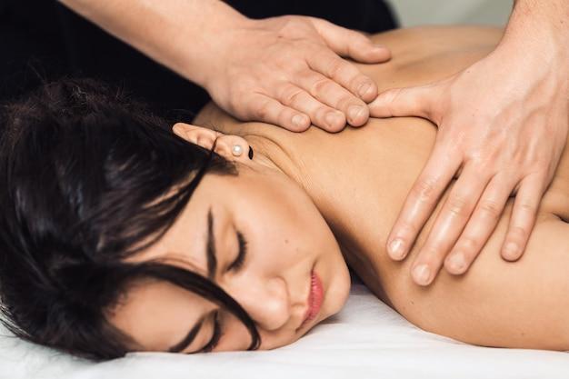 Мужчина массажист делает массаж спины.
