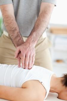 A masseur massages a womans back