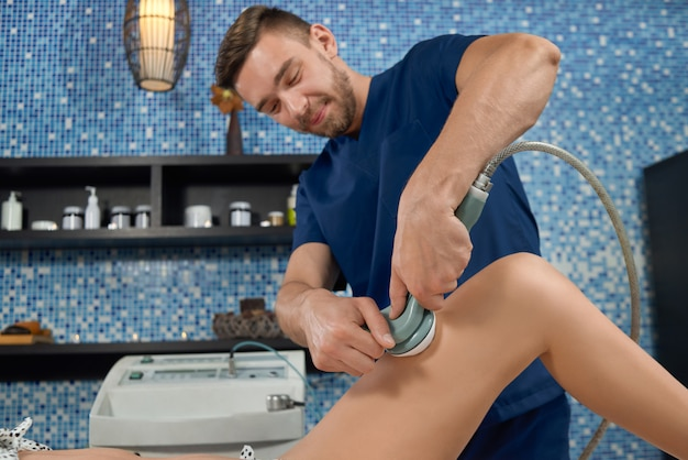 Masseur massaging hips of female with apparatus in spa