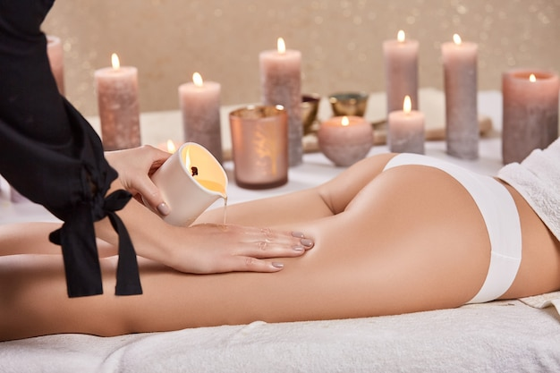 안마사는 왁스를 손에 넣고 촛불 스파 살롱에서 여자 다리와 엉덩이를 마사지