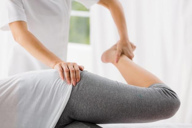 Masseur stretching woman