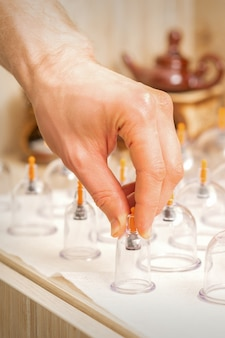 Masseur takes vacuum massage glass jars of traditional chinese cupping therapy from table in spa