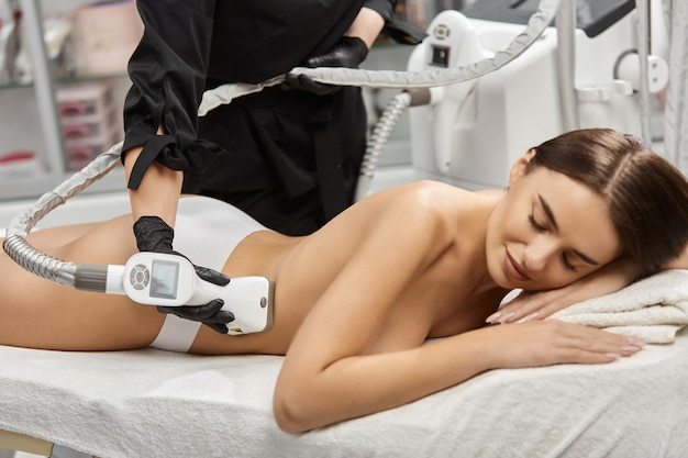 Masseur using anticellulite massager for woman back in beauty salon