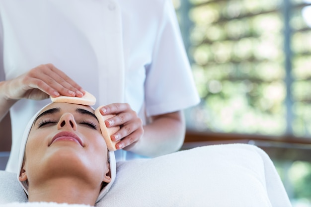 Masseuse cleaning woman face with cotton swabs