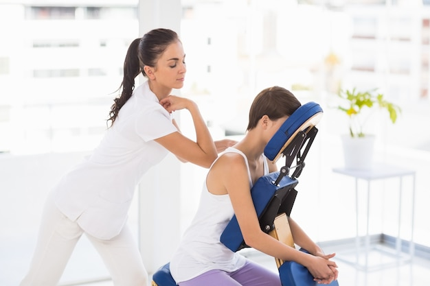 Masseuse giving back massage to woman