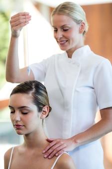 Массажистка держит кулон над головой женщины