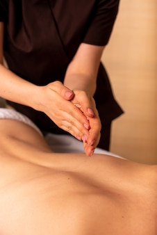 The masseuse rubs her hands with oil before the massage
