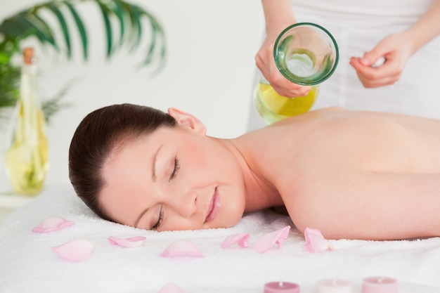 Masseuse versing massage oil on a beautiful woman's back in a spa
