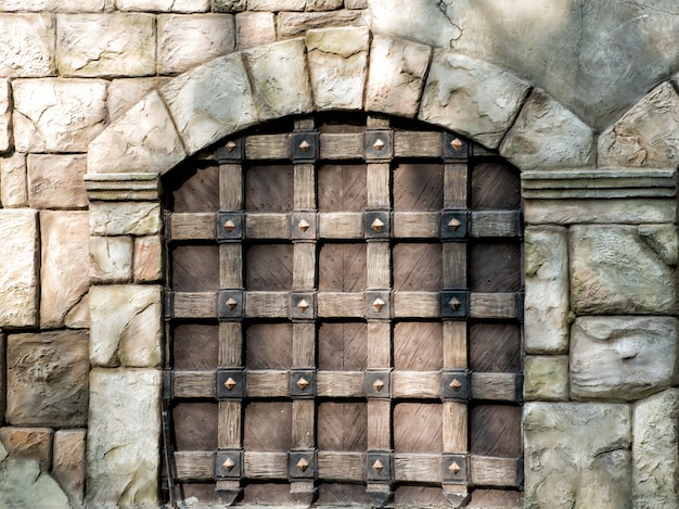 Massive old wooden gate with arch in wall made of large stones